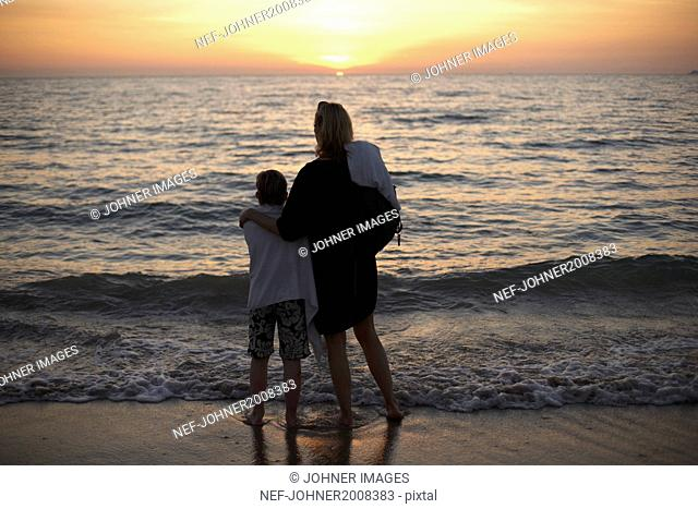 Mother with son watching sunset at sea