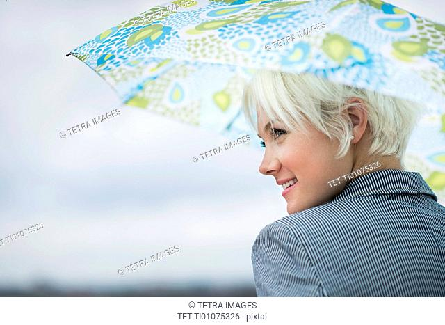 Profile of blonde woman under umbrella