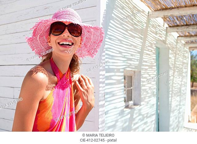 Smiling woman in sunglasses and sunhat