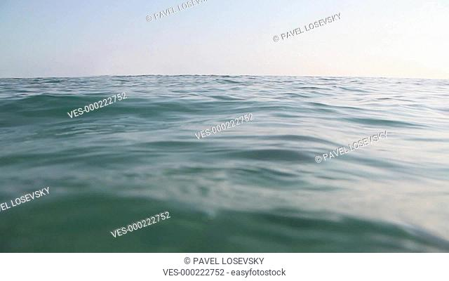 Camera stand close to wavy sea surface and blue sky is at background