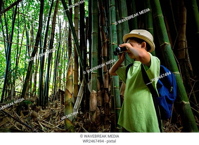 Young boy looking through binoculars in forest