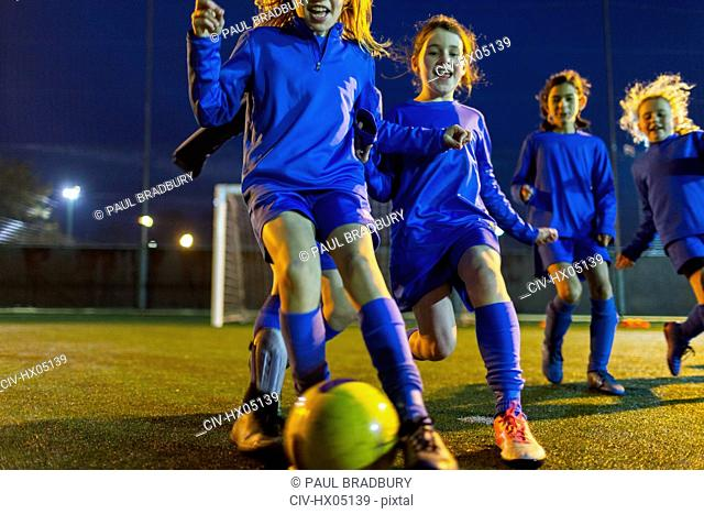 Girls soccer team practicing on field at night