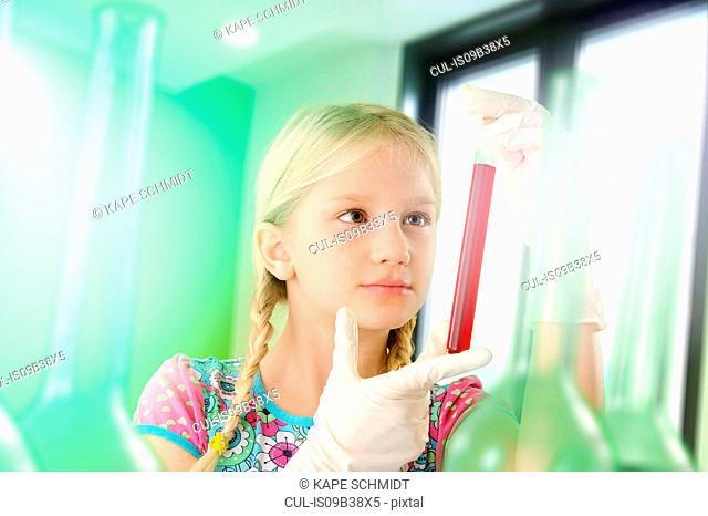 Girl pretending to be scientist examining test tube