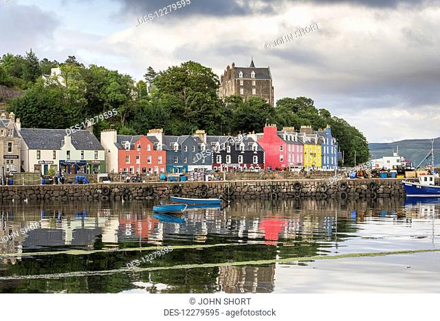 Colourful, buildings along the waterfront with boats moored in the tranquil harbour; Tobermory, Isle of Mull, Argyll and Bute, Scotland