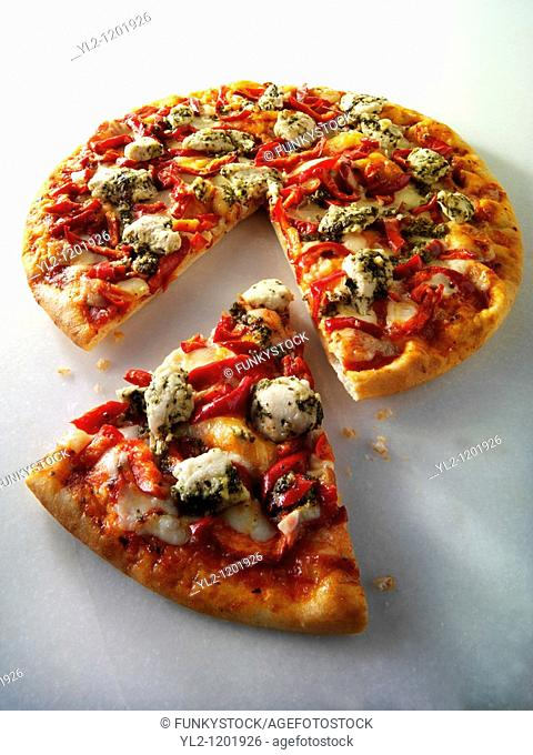 Pizza topped with pesto chicken and red peppers with a slice out