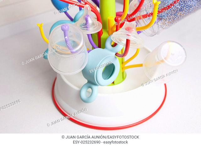 Baby drainer full of plastic tableware objects as baby bottles, nasal aspirator, milk bowls, teats and others