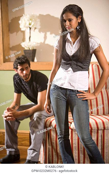 Young man and woman in living room setting, focus on foreground