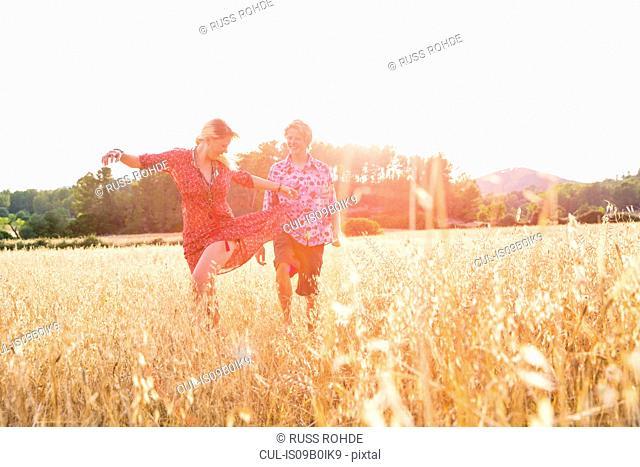 Young woman with boyfriend dancing in wheat field, Majorca, Spain