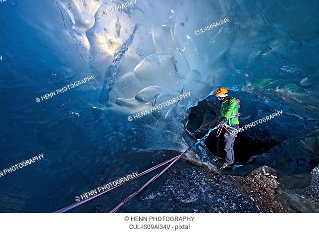 Mature woman descending into Ice cave on the Svinafellsjokull glacier, Vatnajokull National Park, Iceland