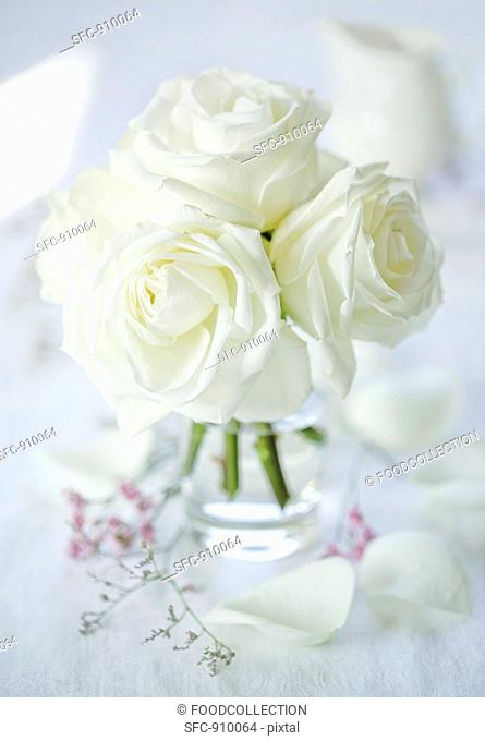 A bunch of white roses in a glass vase