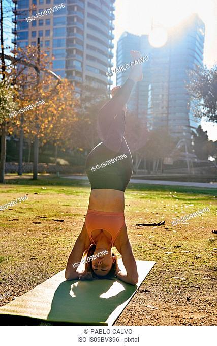 Woman practising yoga in city park, Barcelona, Catalonia, Spain