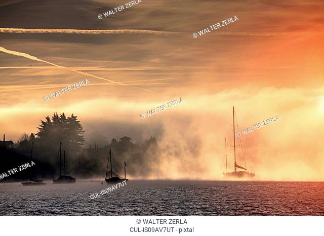 Boats in mist, Lake Maggiore, Piedmont, Lombardy, Italy
