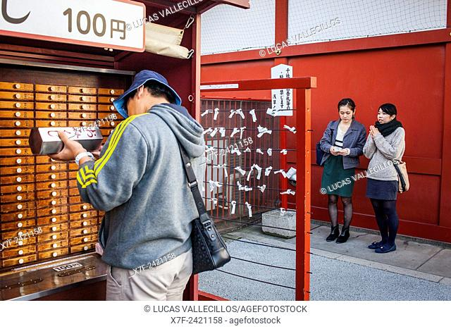At left drawers in a temple containing Omikuji fortune telling papers. Boy looking for his Omikuji. In background girls read their Omikuji
