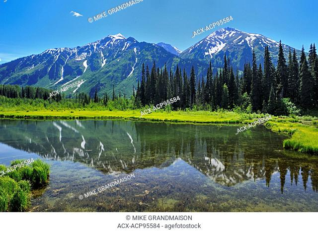 Mountain reflection on the Stewart Cassiar Highway near Bell ll British Columbia Canada
