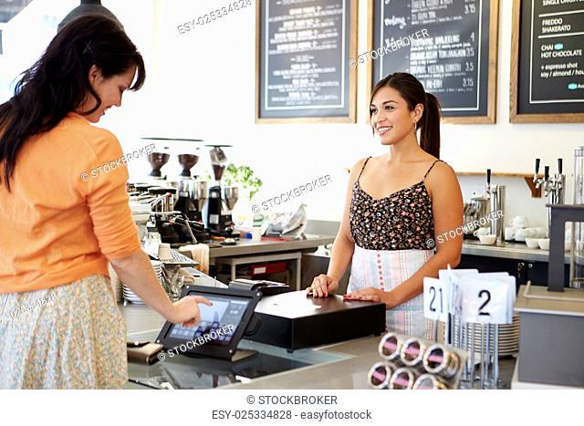 Customer Paying In Coffee Shop Using Touchscreen
