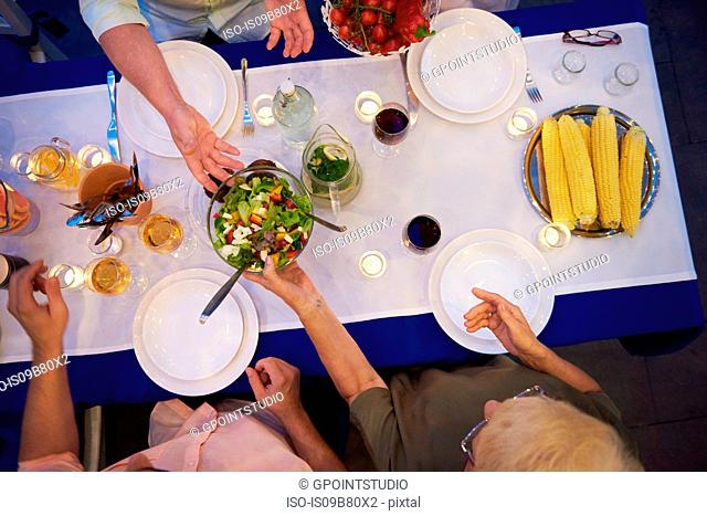 Group of people sitting at table, about to serve food, overhead view