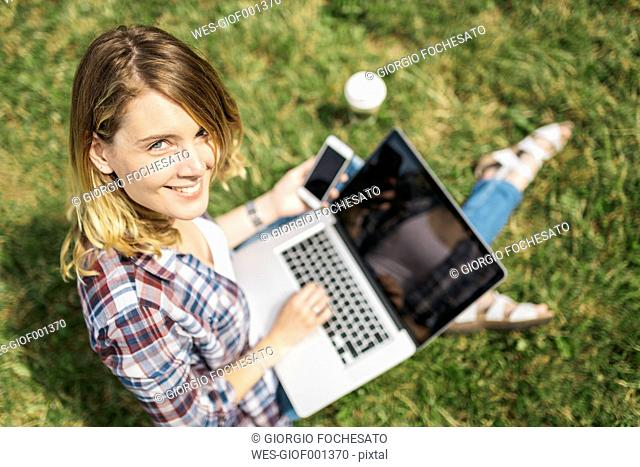 Smiling young woman sitting on a meadow using laptop and smartphone