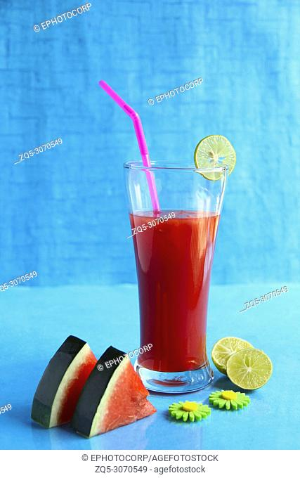 Sliced Watermelon and juice decorated with lemon, isolated on light blue background