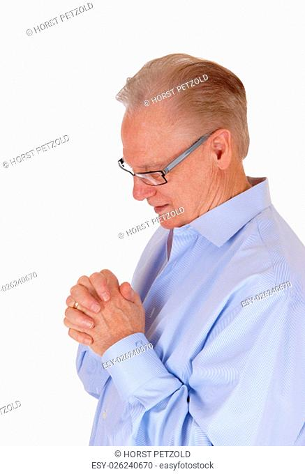A good looking senior man in a blue shirt and his hands felted standing.praying isolated for white background.