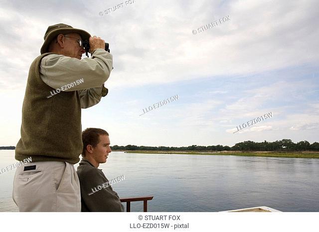 Father and Son Game Viewing on the Zambezi River  Southern Province, Zambia