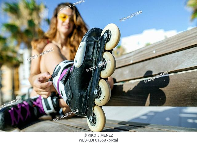 Close-up of woman with inline skates sitting on a bench