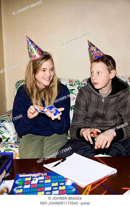 Teenage boy and girl wearing party hat, playing cards