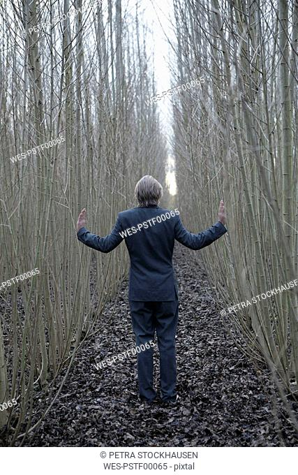 Businessman standing amidst willows