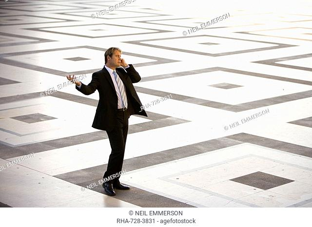 Business man on marble square, Paris, France, Europe