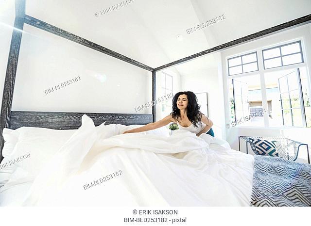 Hispanic woman arranging comforter on bed
