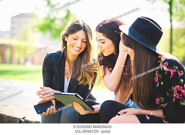 Three young female friends sharing update on digital tablet in park
