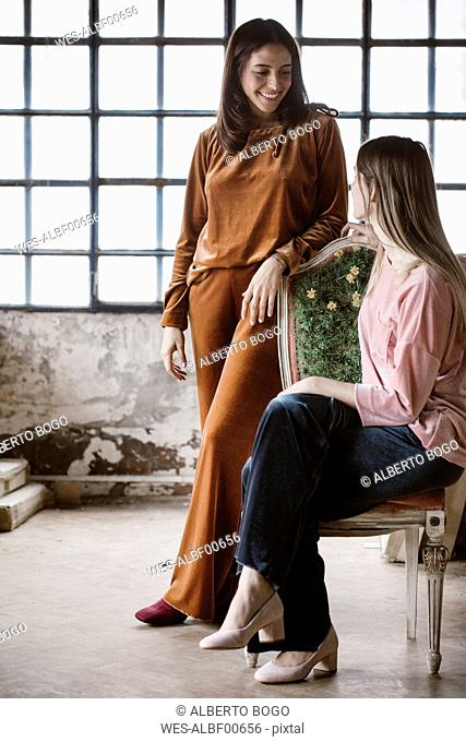 Portrait of fashionabe young woman looking at her friend in a loft