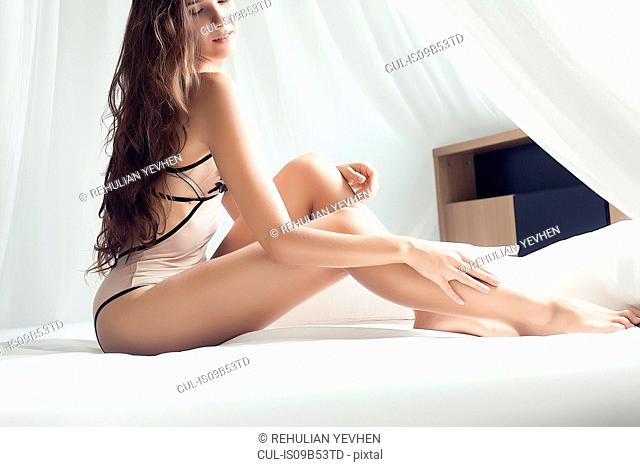 Portrait of young woman wearing swimwear, sitting on bed in provocative pose