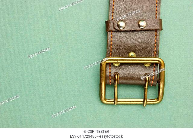 leather belt with a buckle on a green background