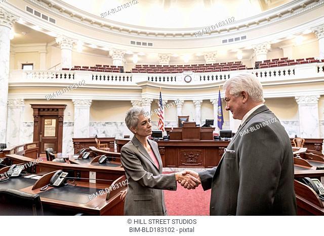 Caucasian politicians shaking hands in capitol building
