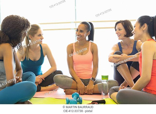 Smiling women talking in exercise class gym studio