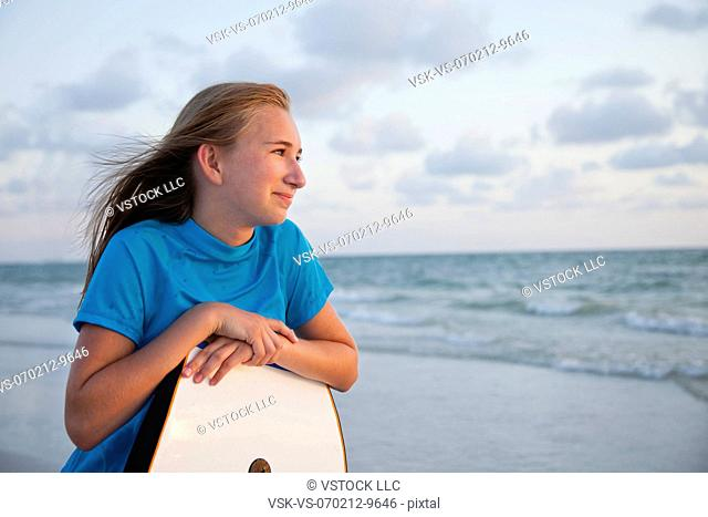 USA, Florida, St. Petersburg, portrait of girl (12-13) leaning on boogie board
