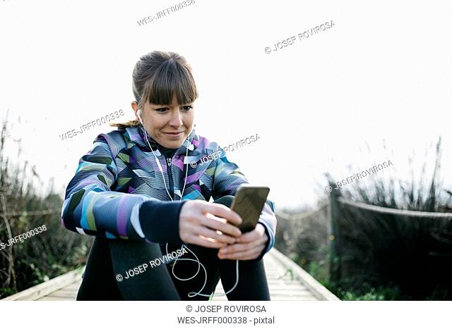 Young woman relaxing after running, using smartphone