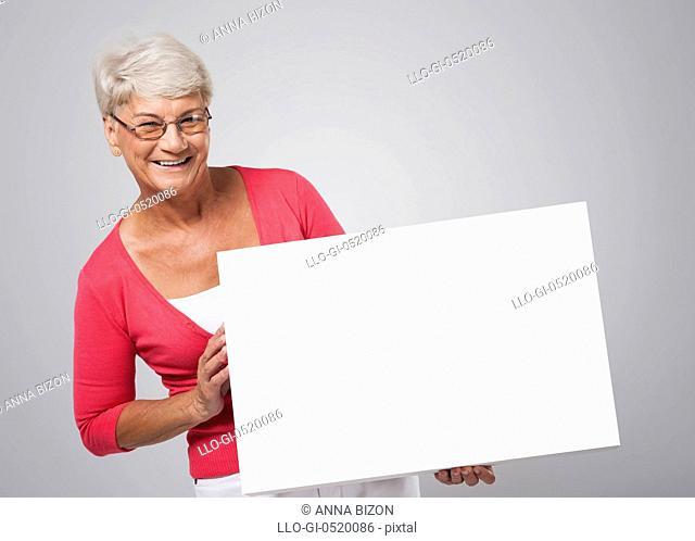 Smiling senior woman holding whiteboard. Debica, Poland