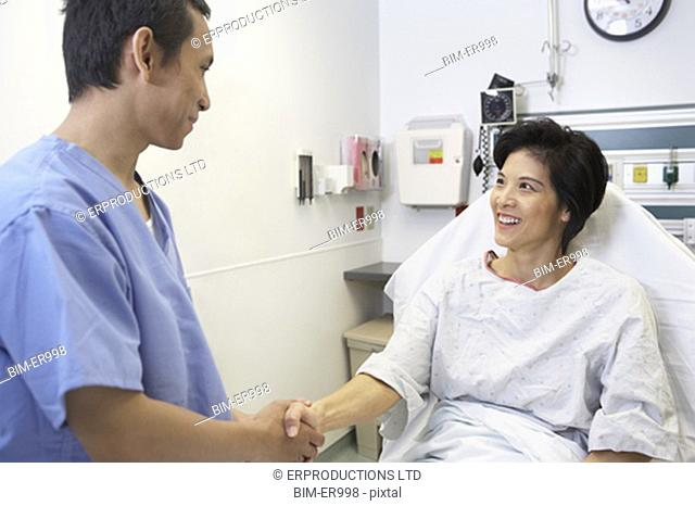 Asian woman in hospital bed shaking hands with doctor