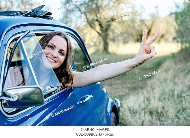 Woman looking out of car window smiling, peace sign, Firenze, Toscana, Italy, Europe