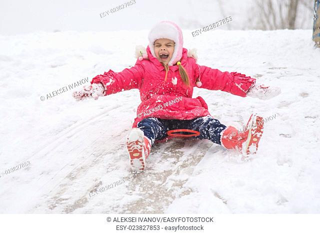 Seven-year girl riding on a snowy icy hill