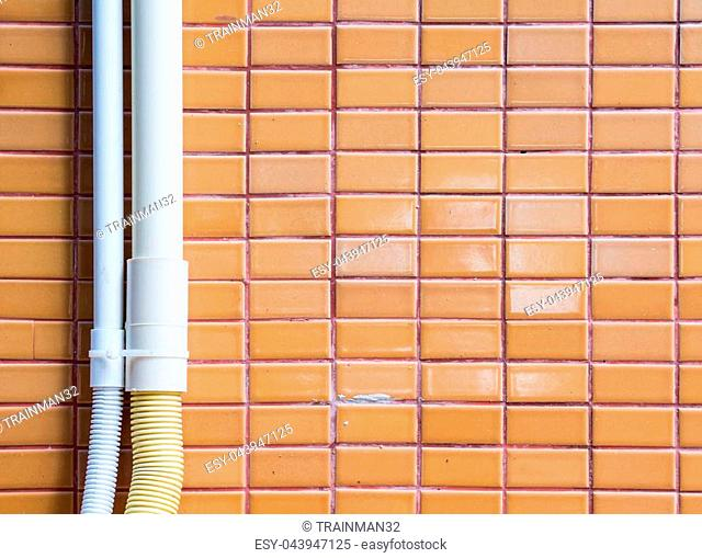 Plastic tube with the electric wire on the tile wall for the light bulb in the factory.(Copy space)
