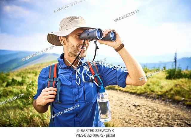 Man looking through binoculars during hiking trip