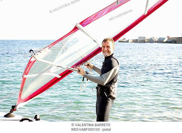 Smiling man windsurfing on the sea