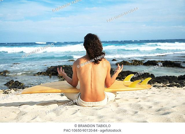 Hawaii, Oahu, young man at the beach meditating with surfboard