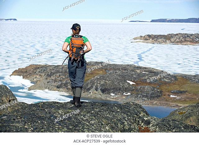 A woman hiking on the shores of the frozen Arctic Ocean, Nunavut