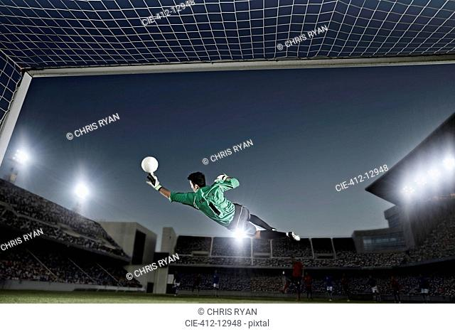 Goalie jumping for ball in soccer net