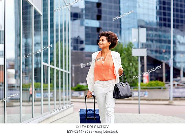 travel, business trip, people and tourism concept - happy young african american woman with travel bag walking down city street