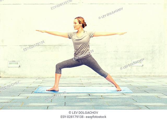 fitness, sport, people and healthy lifestyle concept - woman making yoga warrior pose on mat over urban street background