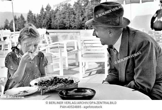 A contemporary postcard shows Adolf HItler on the terrace of his house on the Obersalzberg in Austria next to a blonde girl, who eats cherries